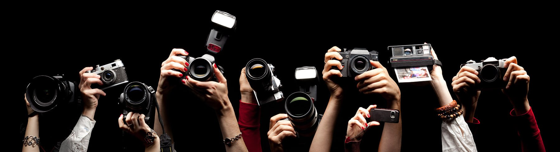 A photograph of different sorts of cameras being held up, as if at a press conference. Only the hands and forearms of the people are visible. The background is black. The image is to suggest a range of different photographers from which you have to select someone for your photoshoot.