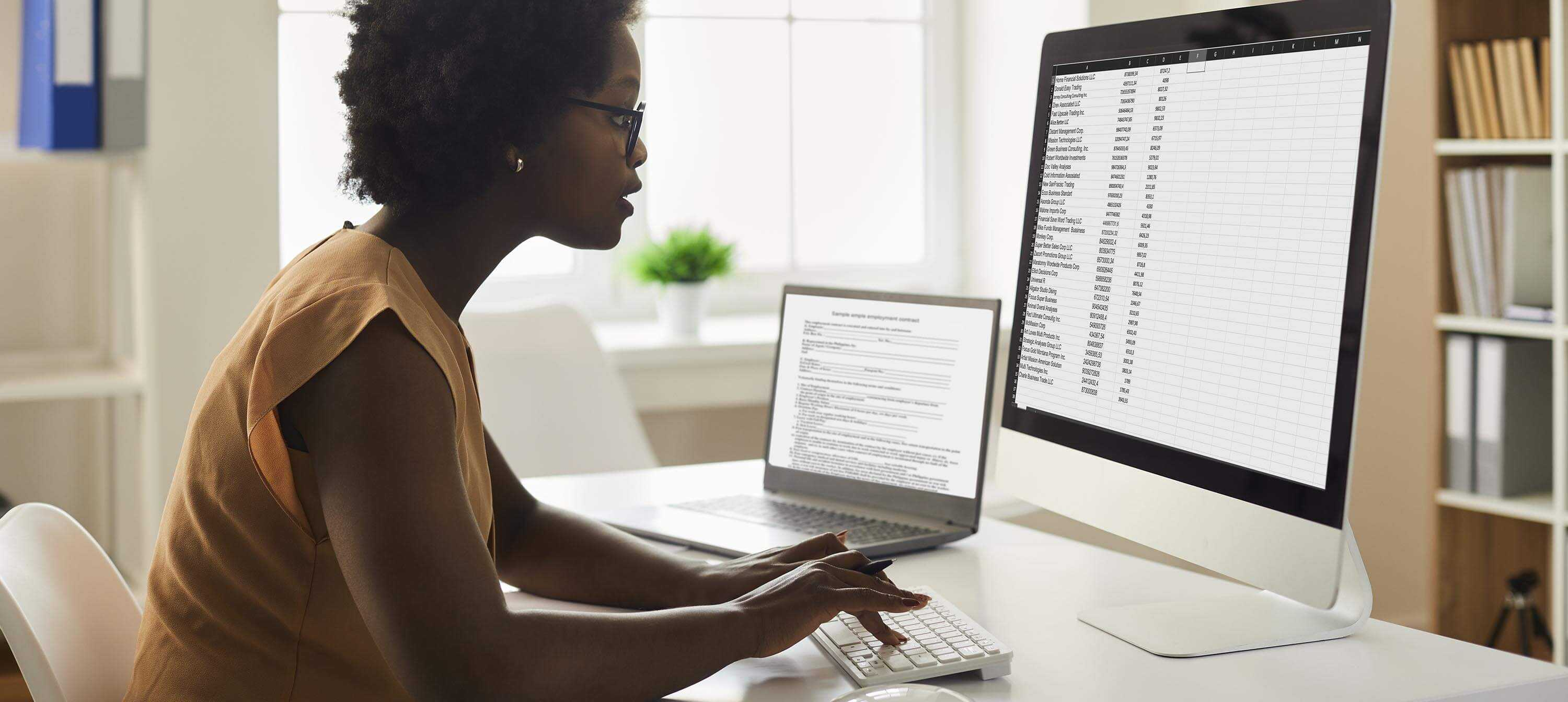 A photo of a woman looking intently at a spreadsheet of data on a large computer screen. She has a laptop open as well on a sleek white desk. In the background, which is slightly blurred, you can see uncluttered, neatly arranged files on shelves, suggesting an office environment. There's a small green plant, in a white pot on the window sill. You can't see out of the window.