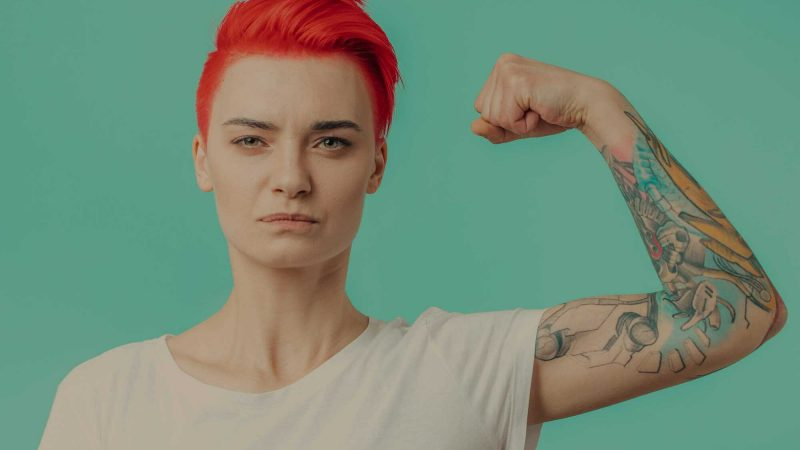 An image of a strong female body builder with short, bright red hair looking straight into the camera lens with a deterimined look in her eyes. She's wearing a white T-shirt which exposes a colourful sleeve tattoo. She is tensing her bicep to show her muscles.