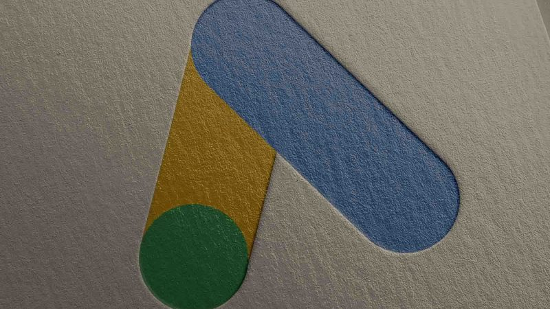 A close up of the Google Ads logo embossed into high quality paper. The logo is a stylised capital letter A, in green, yellow and blue.