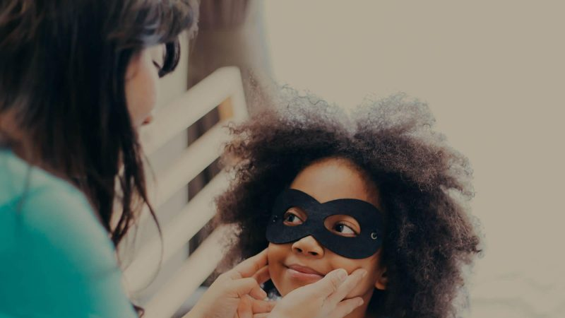A young girl is wearing a plain black superhero mask around her eyes and a cape. She looks happy and is looking with big eyes at an adult whose hands are touching her cheeks after possibly having adjusted her mask.