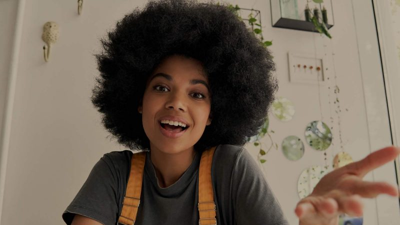 A young woman with a big smile, speaking energetically presumably into a camera. We think she's a social media influencer. She's wearing a grey T-shirt, and orange dungarees. In the background is a white wall with a selection of plants growing down from several small wall-mounted wire and glass terrariums.