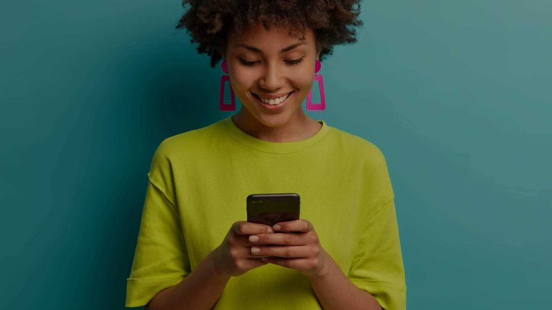 A woman with a lime green T-shirt and bright pink trapezoid shaped earrings is smiling at her mobile phone, taken here to suggest she's pleased with how the website she's viewing is performing on mobile. She's in a pale turquoise background, which makes the pink of her earrings and her T-shirt stand out.