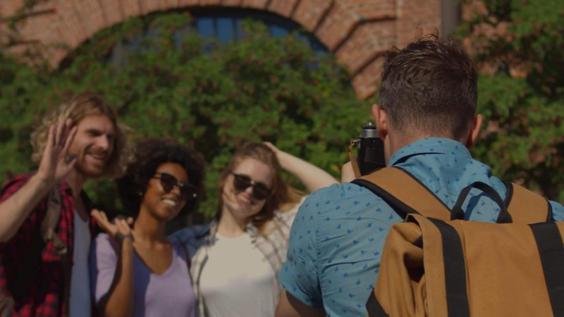 An image of a photography with his back to the camera wearing a blue shirt and a beige and black photographer's rucksack taking a picture of three people outside on a sunny day. The photo is taken in a city with a brick archway and trees slightly blurred in the background.