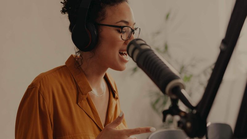 A photo of a young woman wearing an burnt orange coloured blouse speaking into a microphone whilst glancing down at her notes. She's wearing headphones and we think she might be recording a podcast. She's sitting at a wooden table, and there's a plant, blurred, in the background.