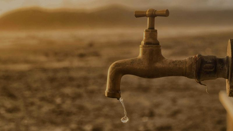 A photo of a brass outdoor tap with a drop of water dripping from its spout. The background is blurred, but is suggestive of a dry, dusty desert. The suggestion here is that a drop of content may be more effective than a larger quantity.