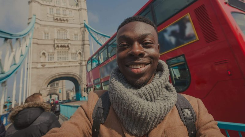 A smiley young man wearing a grey scarf and smart brown coat is posing for a selfie in front of one of the towers of Tower Bridge in London, whilst a red london double decker bus passes behind him. It looks like he's a tourist or a social influencer.