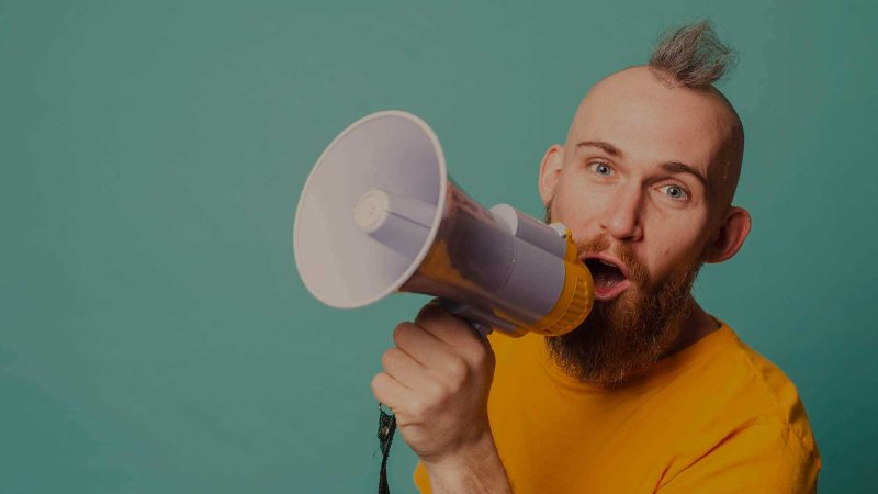 A man with a beard and mohican hair style wearing a yellow T-shirt is looking directly into the camera whilst holding a yellow and white megaphone to his mouth. He's pictured on a plain turquoise background. The image  is being used to suggest a casual tone of voice in corporate communications.