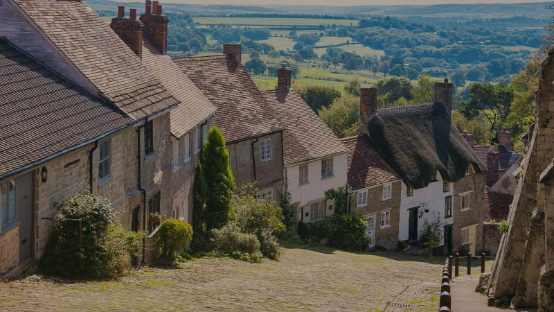 A colour photo of the view from Gold Hill in Shaftesbury, England which is often used in tourism marketing. This popular tourist spot evokes emotions of old England with a mixture of traditional terraced cottages include one thatched cottage down one side of a very steep hill. In the background you can see the English countryside disappearing to the horizon.