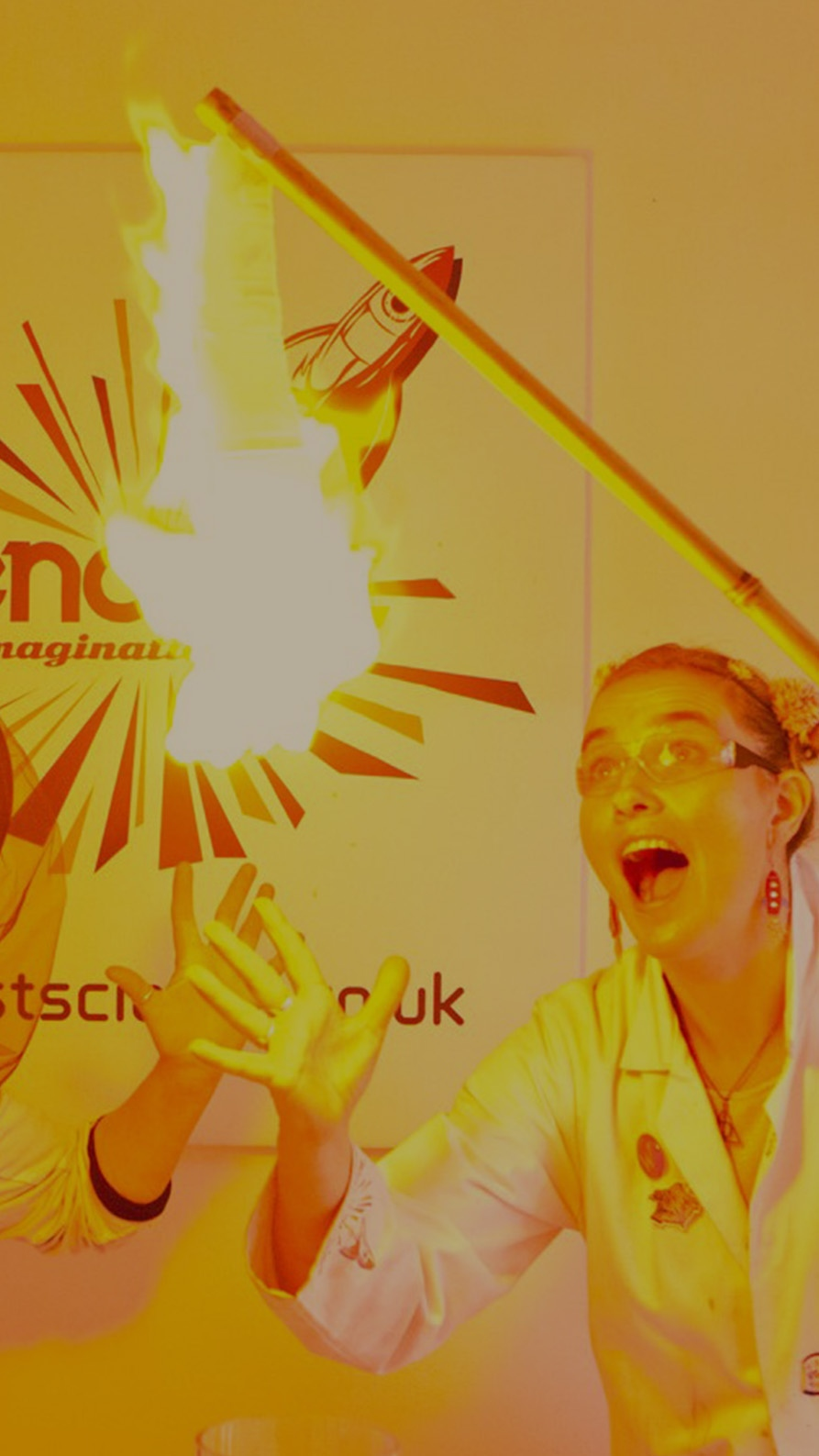Two presenters dressed in lab coats look on excitedly at the small explosion created as a gas is set alight.
