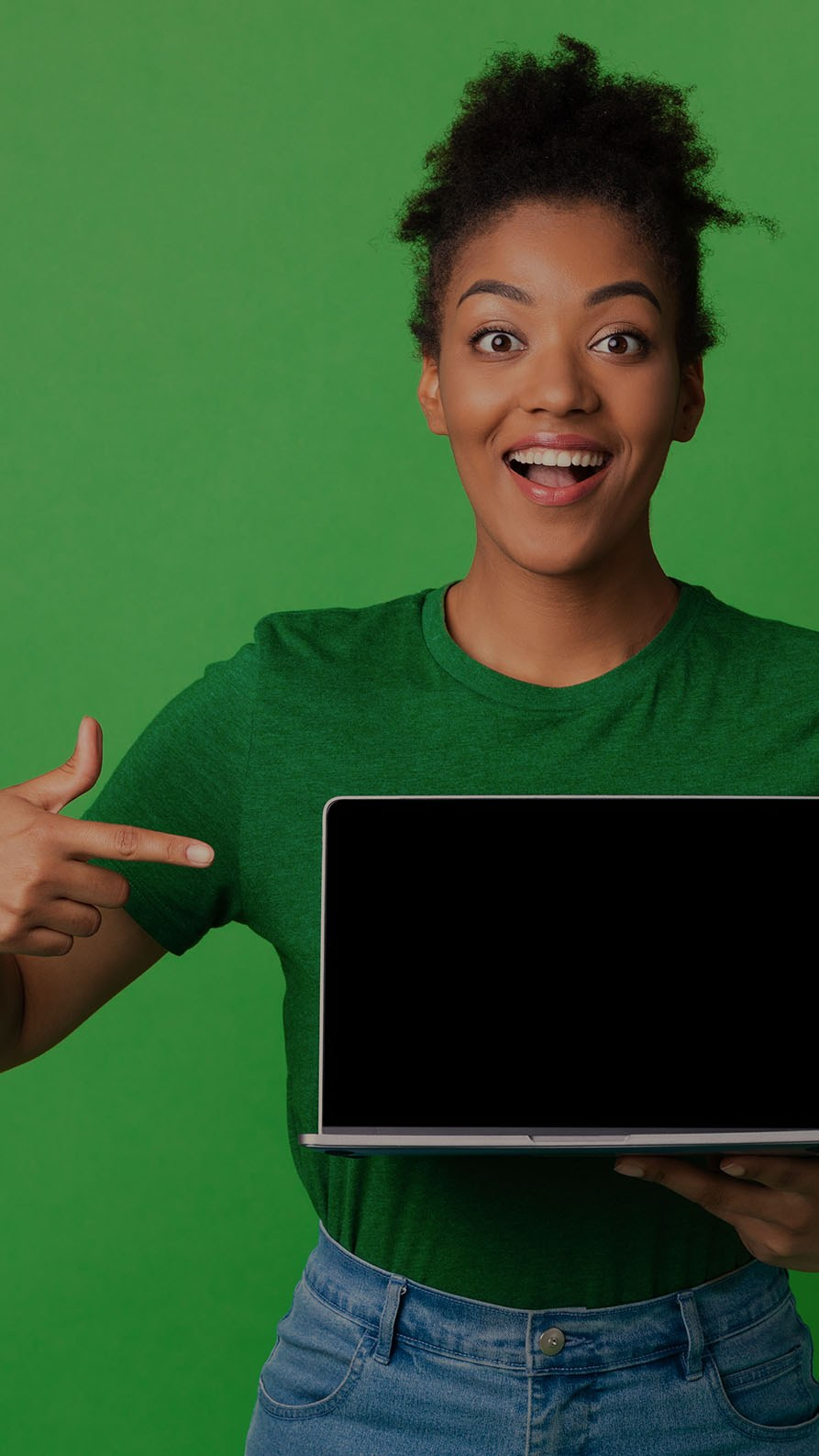 A photo of a woman smiling and pointing to a laptop enthusiastically. She's wearing a dark green T-shirt and there is a plain bright green background behind her. This photo is mildly suggestive that this article may be about websites, but it's all very figurative.