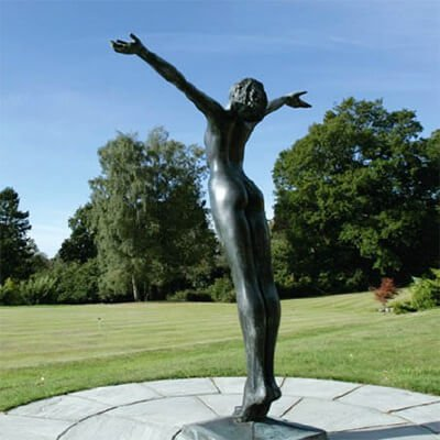 A sculpture in the grounds of Roffey Park, of a nude female figure with arms thrown wide open to the sky.